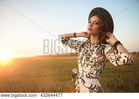 A beautiful romantic girl in a summer dress and hat stands in a field at sunset. Summer and autumn beauty, fashion.