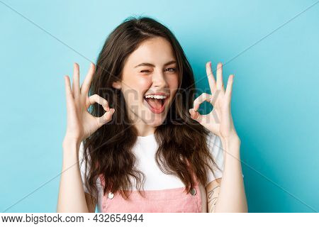 Close Up Of Cheerful Caucasian Woman Agree And Say Yes, Make Alright Okay Sign And Winking Assuringl