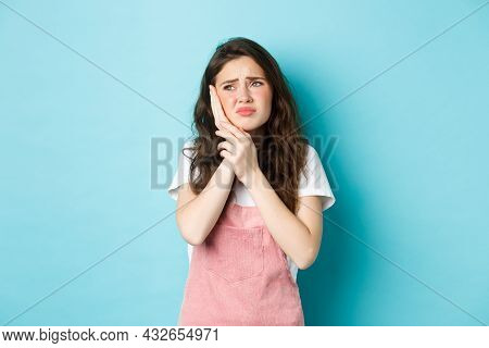 Portrait Of Frowning Girl Touching Cheek, Having Toothache, Looking At Upper Left Corner Stomatology