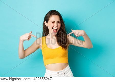 I Am The Best. Smiling Confident Woman Feeling Self-assured, Pointing At Herself And Winking Happy,