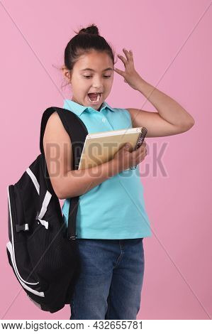 School Girl Holding A Notebook With An Expression Of Astonishment At Watch Her Notebook.