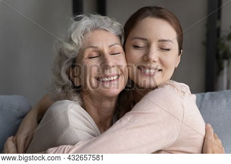 Happy Affectionate Old Mother Cuddling Grown Daughter.