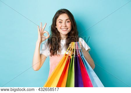 Image Of Happy Young Glamour Woman Shop In Stores With Discounts, Showing Okay Sign, Holding Shoppin