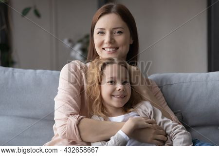 Portrait Of Loving Young Mother Cuddling Little Child Daughter.
