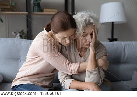 Worried Stressed Young Woman Supporting Unhappy Old Mother.