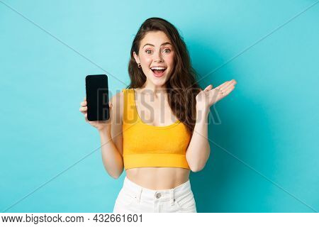 Attractive Young Woman In Glamour Summer Clothes, Showing Empty Smatphone Screen, Gasping Amazed, Re