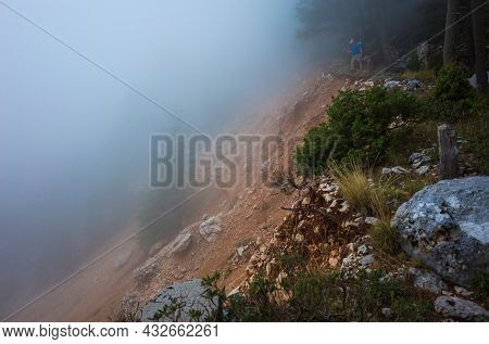 Hiking on Lycian way. Atmospheric landscape of old landslide on mountain forest with thick fog and hiker standing on edge of ravine, Tahtali mountainside on Lycian Way trail, Ecotourism in Turkey