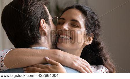 Close Up Happy Hispanic Wife Cuddling Beloved Husband