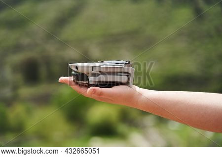 Modern Small Compact Quadcopter In A Girls Hand. Launching A Drone From Your Hand