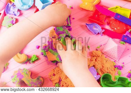 Hands Of A Child Playing With Multicolored Kinetic Sand.
