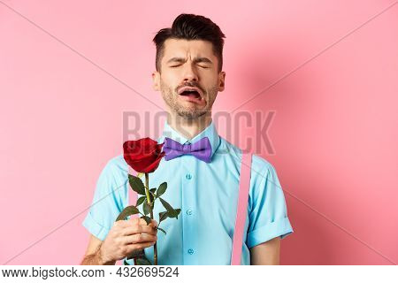 Heartbroken Guy In Funny Bow-tie Crying Over Girlfriend, Standing Alone With Red Rose On Pink Backgr