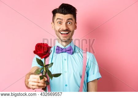 Valentines Day And Romance Concept. Happy Smiling Man Giving You Red Rose On Romantic Date, Standing