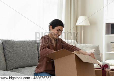 Overjoyed Young Female Of Indian Ethnicity Unpacking Box With Gifts