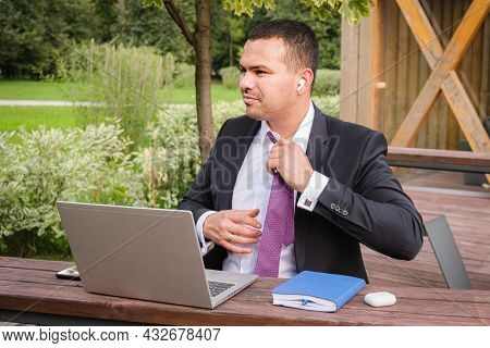 Serious Young Man In Business Suit Takes Off His Tie After Finishing Work On Open Veranda. Business
