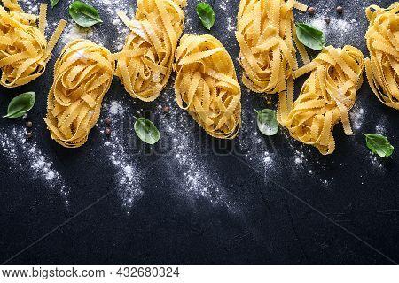 Tagliatelle. Homemade Pasta, Basil Leaves, Flour, Pepper, Olive Oil And Cherry Tomato On Dark Black