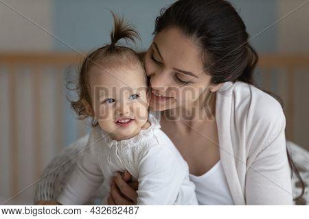 Happy Mom Cuddling Cute Baby, Hugging, Kissing Little Daughter Girl