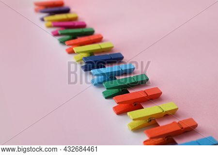 Many Different Colorful Clothespins On Pink Background. Diversity Concept