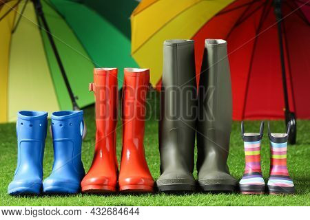 Rainboots For All Family Members On Green Grass