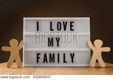 Wooden Figures And Lightbox With Phrase I Love My Family On Table