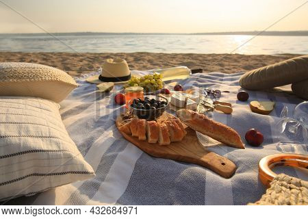 Different Tasty Snacks And Wine On Picnic Blanket Near River