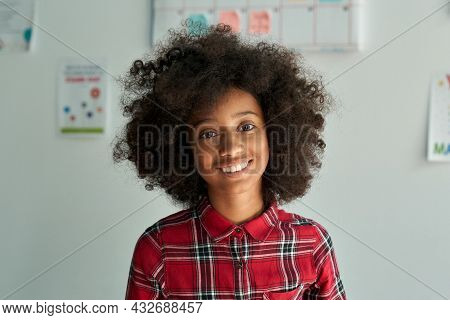 Happy Cheerful Smiling Cute African American Schoolgirl Standing Posing In Classroom On White Wall B