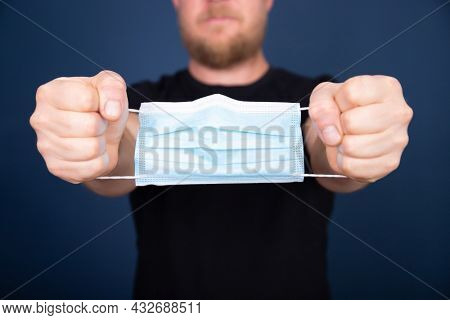 Medical mask as handcuffs on man hands.