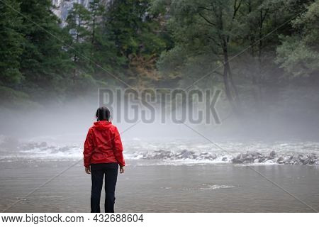 Contact with nature. Woman in raincoat with open arms contemplating nature. Environmental awareness.