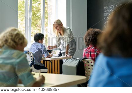 Smiling Young Blonde Teacher Tutor Explains Lesson To Schoolboy Using Tablet Device Teaching Mathema