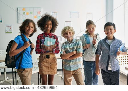 Portrait Of Cheerful Smiling Diverse Schoolchildren Standing Posing In Classroom Holding Notebooks A