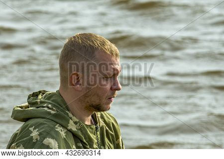 Unshaven Fisherman Against Background Of Waves On River Looks Forward. Side View. In Nature, Outdoor