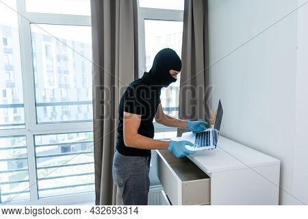 Thief With Black Balaclava Stealing Laptop. The Burglar Commits A Crime In Luxury Apartment