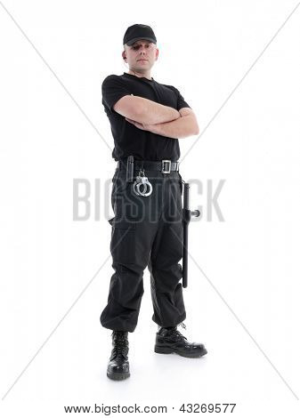 Security man wearing black uniform equipped with police club and handcuffs standing confidently with arms crossed, shot on white