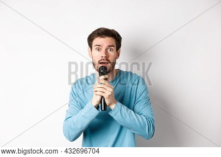 Confused Young Man Looking Nervously At Camera While Singing Karaoke, Holding Microphone, Standing O