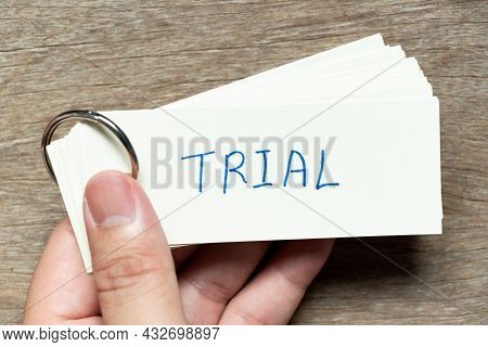 Man Hold The Flash Card With Handwriting Word Trial On Wood Background