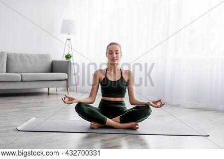 Calm Serene European Pretty Millennial Blonde Lady Practicing Yoga, Sitting In Lotus Position Alone