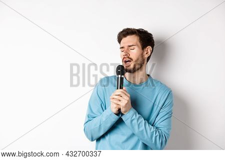 Young Caucasian Man Singing Song In Microphone With Carefree Face, Standing In Karaoke Over White Ba