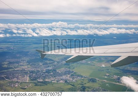 View Through Airplane Porthole With Fields Landscapes, Cloudscape Sky, Light Clouds And Part Of Airp