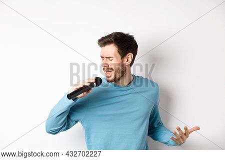 Singer Performing Song On White Background. Young Man Singing In Microphone At Karaoke