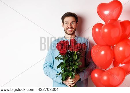 Valentines Day Romance. Excited Young Man With Bouquet Of Red Roses And Heart Balloons Smiling At Ca
