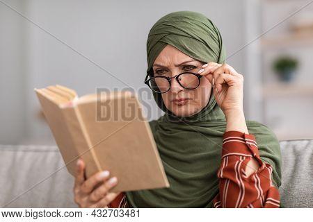Senior Muslim Woman Having Poor Eyesight Reading Book At Home