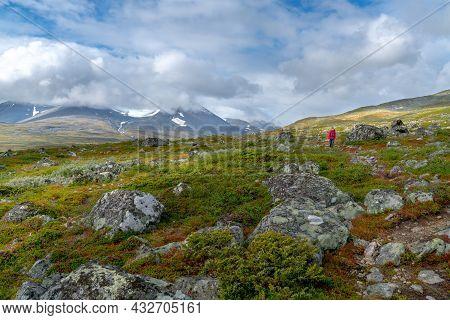 Female Hiker In Red Jacket, Walking Through Remote Arctic Terrain Of Swedish Lapland In Stora Sjofal