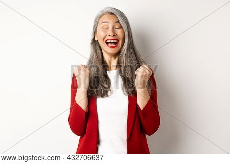 Relieved Asian Senior Businesswoman Making Fist Pump, Saying Yes And Smiling Satisfied, Triumphing A
