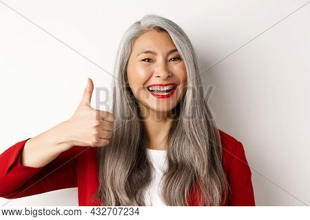 Close-up Of Happy Asian Female Manager In Red Blazer, Showing Thumb-up And Smiling In Approval, Like