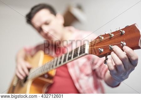 Young Man Tuning A Guitar At Home, Detail Shot, Focus In The Hand And The Headstock.