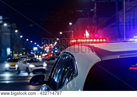 Police Car Lights At Night In City With Selective Focus And Blurry Car Traffic In The Bokeh
