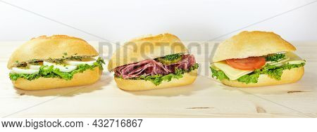 Row Of Three Sandwich Rolls With Egg, Salami And Cheese On A Wooden Table Against A Light Background