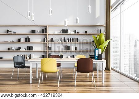 Modern Panoramic Office Interior With Bright Chairs, A Table, Pendant Lights And A Shelving Next To
