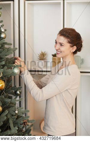 Happy Young Caucasian Woman In Sweater Decorating Christmas Tree With Balls Against Shelves With Pot