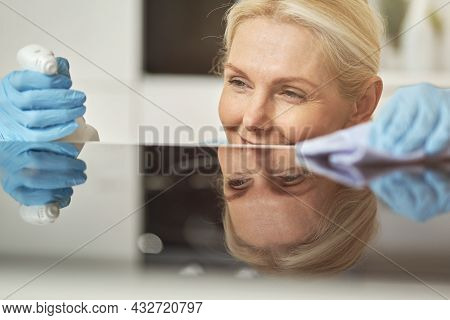 Close Up Portrait Of Pleased Mature Blonde Woman In Rubber Gloves Cleaning Cooktop In The Kitchen Us