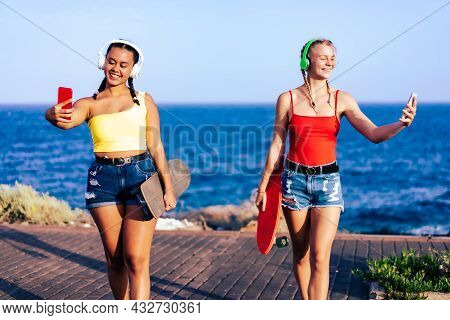Multiracial Girls Walking And Listenig The Music, Having Fun Outdoor. Lifestyle Concept.